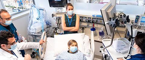UCSF medical workers attend to UCSF patient relations manager Amy Hyams, a mock patient, during a Day in the Life drill for UCSF's Mt. Zion COVID-19 ward on Monday, April 27, 2020. From left to right are respiratory care practitioner Gary Dunne, Dr. John Turnbull, Dr. Christy Inglis-Arkell, Hymans and nurse Sarah Berger. (Photo by Noah Berger