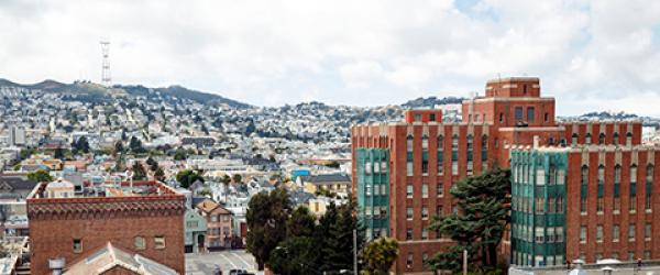view of older Zuckerberg San Francisco General Hospital brick buildings, with SF streets and buildings in background